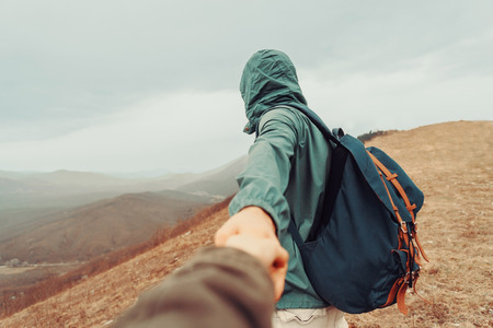 focus shot: Traveler man holding womans hand and leading her on nature outdoor. Focus on man. Point of view shot Stock Photo
