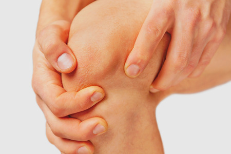 Der Mann berührt das Kniegelenk auf Grund akuten Schmerzen auf weißem Hintergrund Standard-Bild