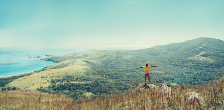 outstretched arms: Traveler man standing with raised arms on peak of mountain near the sea and enjoying beautiful landscape in summer Stock Photo
