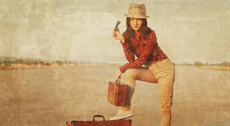 Femme voyageur avec des jumelles et valise sur la route. Image vintage