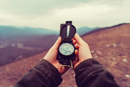 female hand: Hiker woman searching direction with a compass in the mountains. Point of view shot