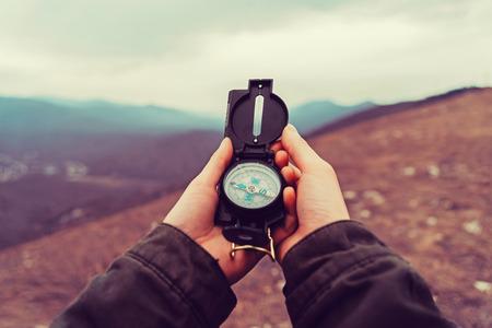 Turystą kobieta kierunek poszukiwania z kompasem w górach. Punktu widzenia strzał