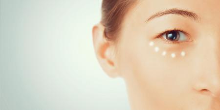 Portret młodej kobiety z kremem wokół koncepcji oczu, kosmetyki i pielęgnacji skóry