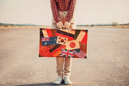 Traveler woman with a suitcase standing on road. Suitcase with stamps flags of different country