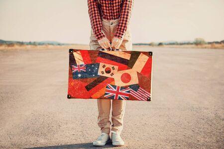 mujer con maleta: Mujer viajero con una maleta que se coloca en la carretera. Maleta con sellos de banderas de diferentes pa�ses