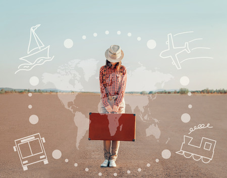 Traveler young woman standing with a suitcase on road. Map of the world and types of transport on image. Concept of travel 免版税图像