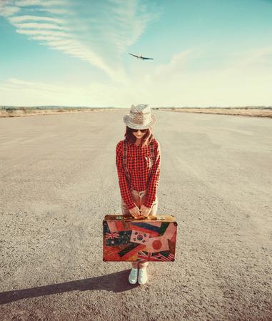 Podróżnik kobieta trzyma rocznika walizkę na pasie startowym