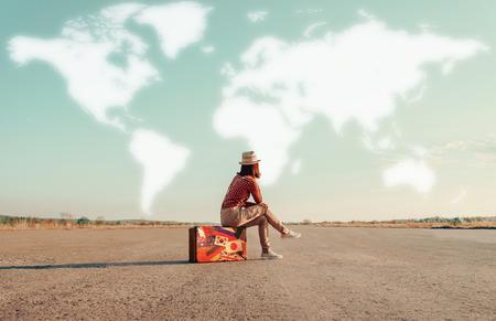 旅行: 旅行者の女性スーツケースの上に座ってと冒険を夢見ています。世界の地図を空に描かれています。旅行のコンセプト