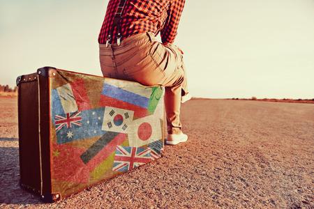 Kobieta turysta siedzi na walizka na drodze. Walizka z znaczkami flagi różnych krajów. Pojęcie podróży