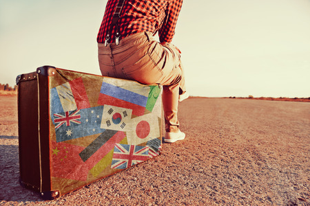 leave: Tourist woman sitting on a suitcase on road. Suitcase with stamps flags of different countries. Concept of travel