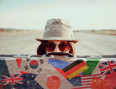 Hipster girl in a hat and sunglasses looks out from vintage suitcase. Suitcase with stamps flags of different country 免版税图像