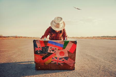 femme valise: Voyageurs femme � la recherche de quelque chose dans le plein air de valise ouverte. Avec filtre mill�sime