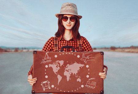 Smiling traveler woman holding suitcase. Map of the world and types of transport on a suitcase. Concept of travel photo