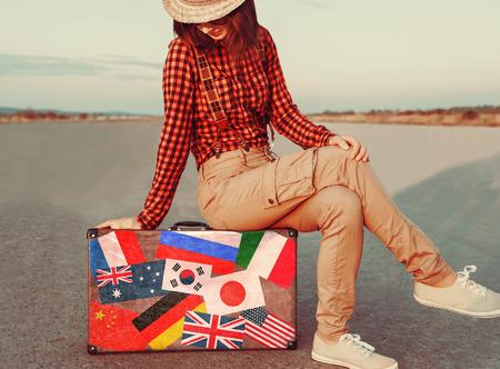 femme valise: Voyageurs jeune femme assise sur la valise. Valise avec timbres drapeaux de diff�rents pays. Concept de Voyage Banque d'images
