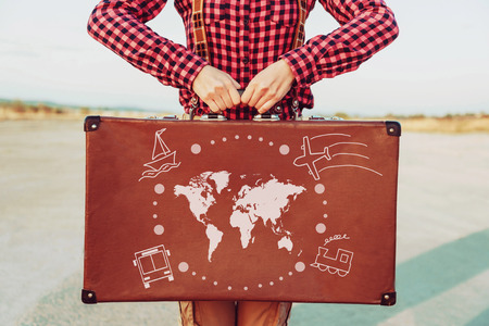 vacation map: Traveler woman standing with a suitcase. Map of the world and types of transport are painted on suitcase. Concept of travel