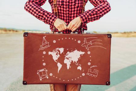 Viajante da mulher que está com uma mala de viagem. Mapa do mundo e tipos de transporte são pintados na mala de viagem. Conceito de viagem