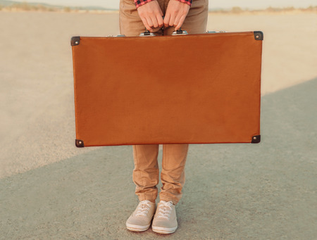 Traveler holding a suitcase, view of hands. Space for text on suitcase