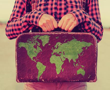 mundo manos: Viajero de la mujer joven que sostiene una pequeña maleta. Maleta con sellos de banderas de diferentes países Foto de archivo