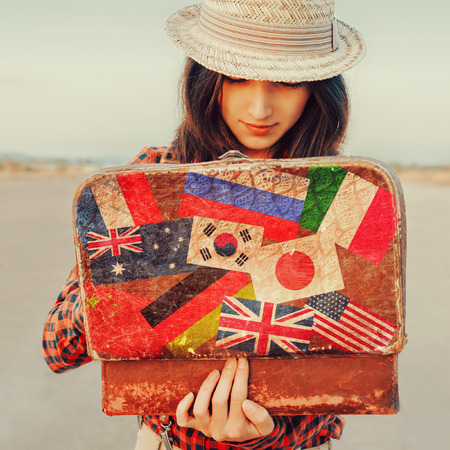 country girls: Young beautiful woman looking for something in the open suitcase. Suitcase with stamps flags of different countries. Concept of travel Stock Photo
