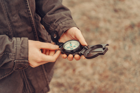 woman searching: Hiker woman searching direction with a compass outdoor. View of hands