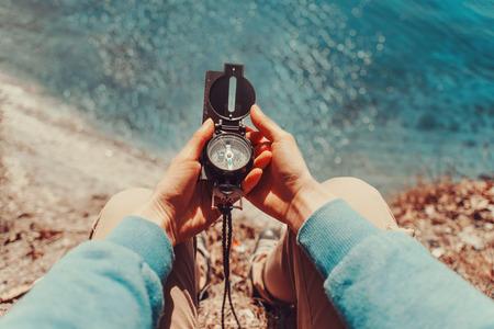 aventura: Mujer viajero en busca de dirección con una brújula en la costa cerca del mar. Punto de vista de tiro