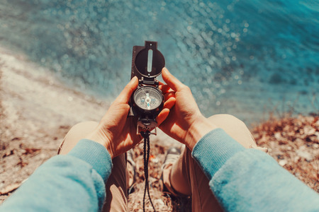 directions: Traveler woman searching direction with a compass on coastline near the sea. Point of view shot