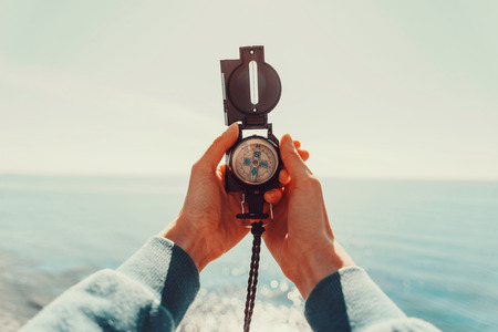 direction: Traveler woman searching direction with a compass on background of sea. Point of view shot