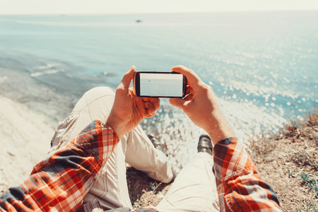 Traveler man taking photographs sea with smartphone. Point of view shot Standard-Bild