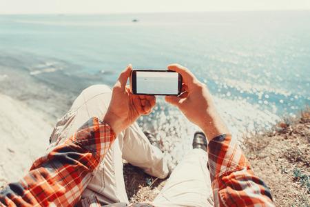 Traveler man het nemen van foto's zee met smartphone. Point of view schot