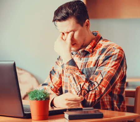 exhausted worker: Tired young man sitting over laptop in the office and rubbing his eyes Stock Photo
