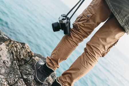 walking boots: Traveler woman with old photo camera standing on stone coast near the sea. View of legs