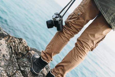 personas caminando: Viajero de la mujer con c�mara de fotos antiguas de pie a costa de piedra cerca del mar. Vista de las piernas
