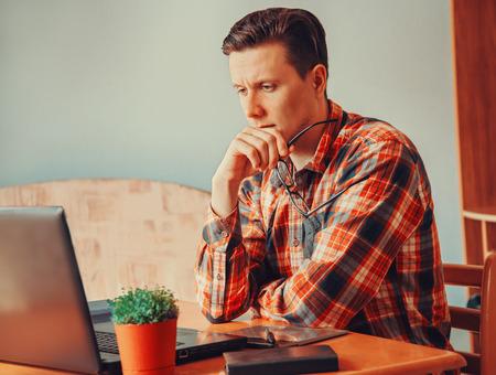 pensamiento creativo: Hombre joven que piensa y que mira en la computadora port�til en la oficina