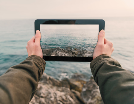 takes: Woman taking photographs coast on tablet PC. Point of view shot