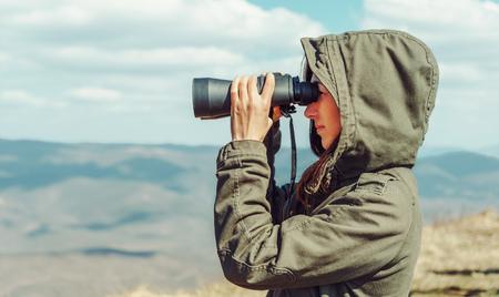 binoculars view: Hiker woman looking in binoculars in the mountains, side view Stock Photo