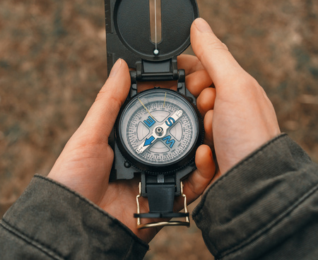 Female traveler holding a compass on nature. Point of view shot. Close-up image