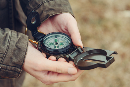 woman searching: Hiker woman searching direction with a compass outdoor. View of hands. Close-up image