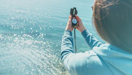 brujula: Mujer viajero en busca de dirección con una brújula en la costa cerca del mar en verano. Vista trasera