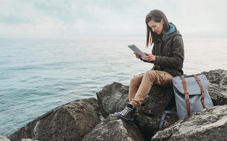 travel: Dziewczyna samotnie siedzi na wybrzeżu w pobliżu morza i pracy na cyfrowym tablecie