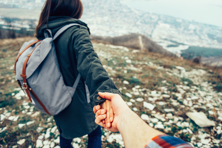 Hiker young woman holding mans hand and leading him on nature outdoor. Stock Photo