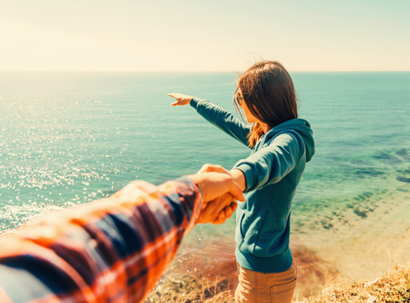 filters: Couple in love. Beautiful young woman holding mans hand and showing him something in distance the sea.