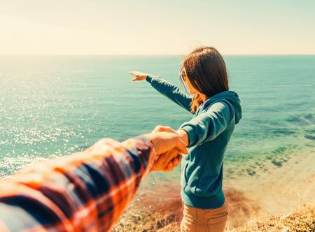 cheerful woman: Pareja de enamorados. Mujer joven hermosa que sostiene la mano del hombre y lo que muestra algo en la distancia al mar. Foto de archivo
