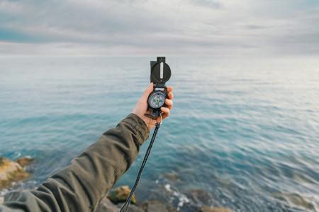 brujula: Buscar viajero dirección con una brújula en la costa cerca del mar en verano. Punto de vista Foto de archivo