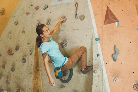 free climber: Free climber young woman climbing artificial boulder indoors