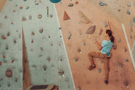 free climber: Free climber young woman climbing artificial boulder in gym