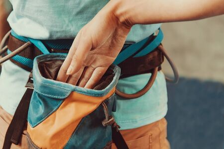 magnesia: Climber woman putting her hand in the bag of powder magnesia, close-up