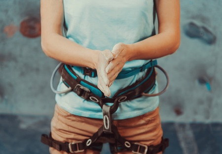 Climber woman coating her hands in powder chalk magnesium and preparing to climb indoor, close-up Stock Photo - 39633326
