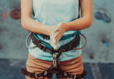 escalando: Mujer escalador recubriendo sus manos en forma de polvo de tiza de magnesio y se prepara para subir de interior, primer plano Foto de archivo