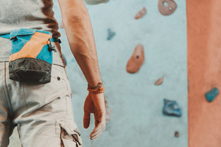 rock climbing: Young man standing in front of a practical climbing wall indoor and preparing to climb, close-up