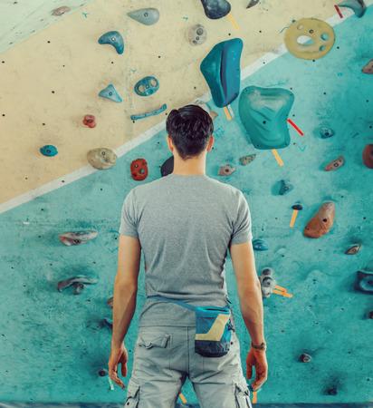 Jonge man staande voor een praktische klimmuur binnen en het voorbereiden om te klimmen